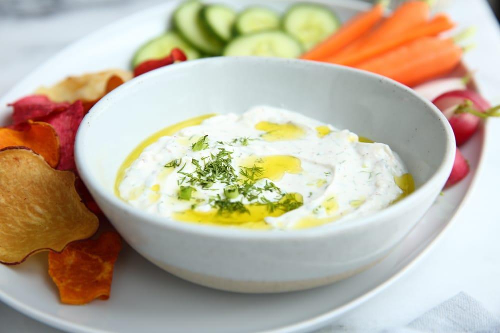 Yogurt feta dip in bowl with chips and veggies on platter