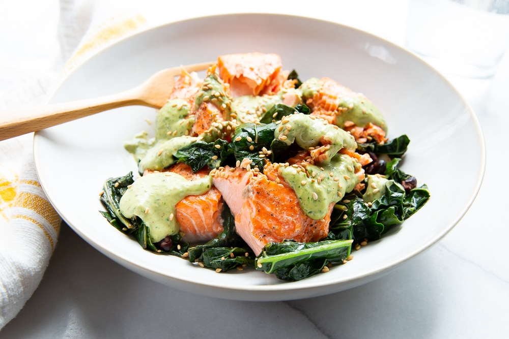 Roasted kale and salmon bowls drizzled with green tahini sauce.