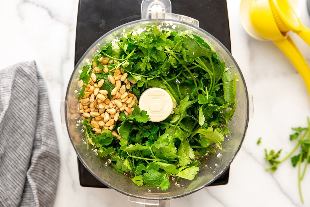 Process shot showing herbs, garlic and pine nuts in food processor