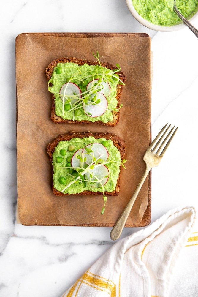 Creamy Pea Dip on toasted bread with radishes and pea shoots