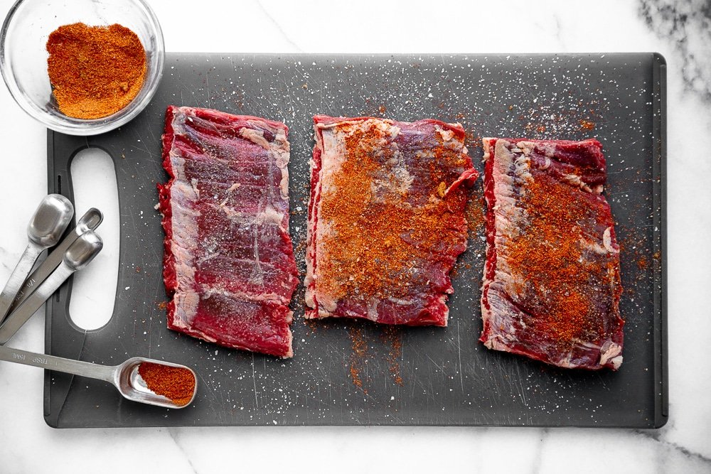Uncooked skirt steak cut into thirds on cutting board, sprinkled with spice rub