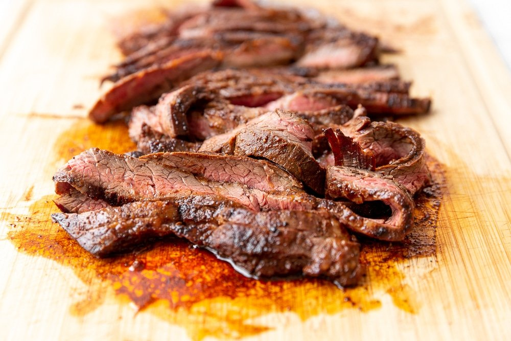 Cooked skirt steak sliced on cutting board, ready to go into the ultimate steak burrito bowl
