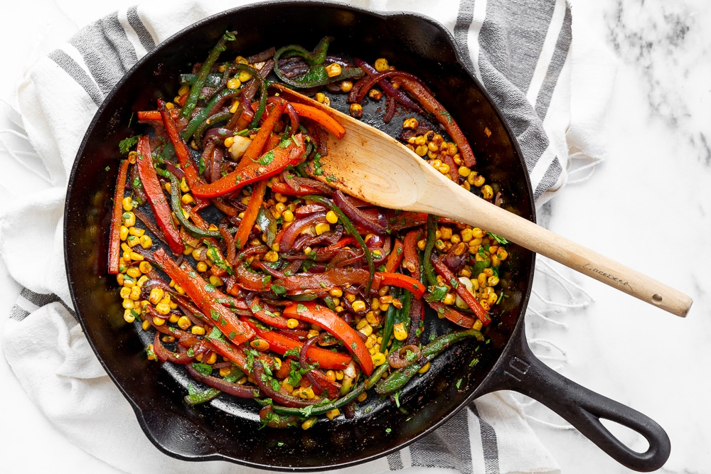 Onions, peppers and corn in cast iron skillet for the steak burrito bowls