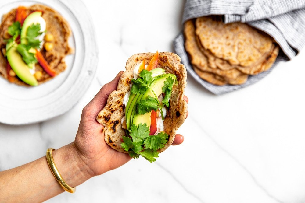 Taco in a hand with a stack of cassava tortillas in the background