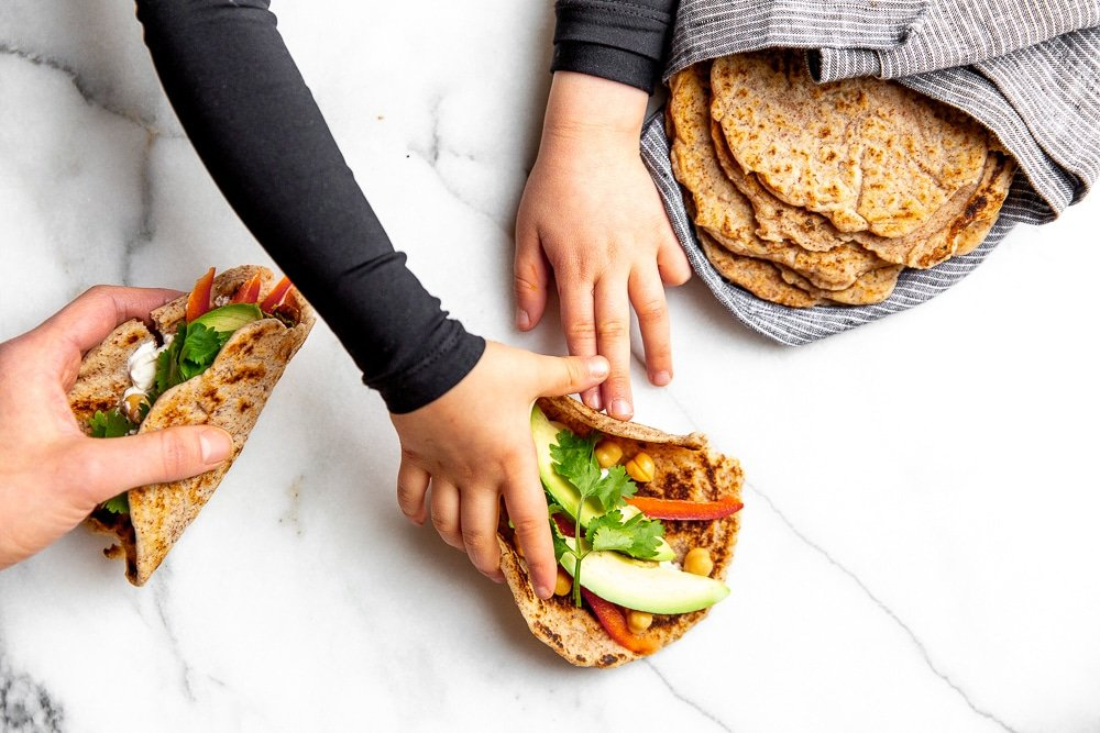 Hands on the counter grabbing tacos made with cassava tortillas.