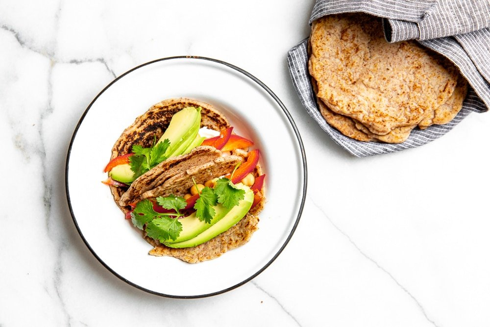 Vegetable tacos on a plate made with cassava tortillas, with a stack of tortillas on the side.