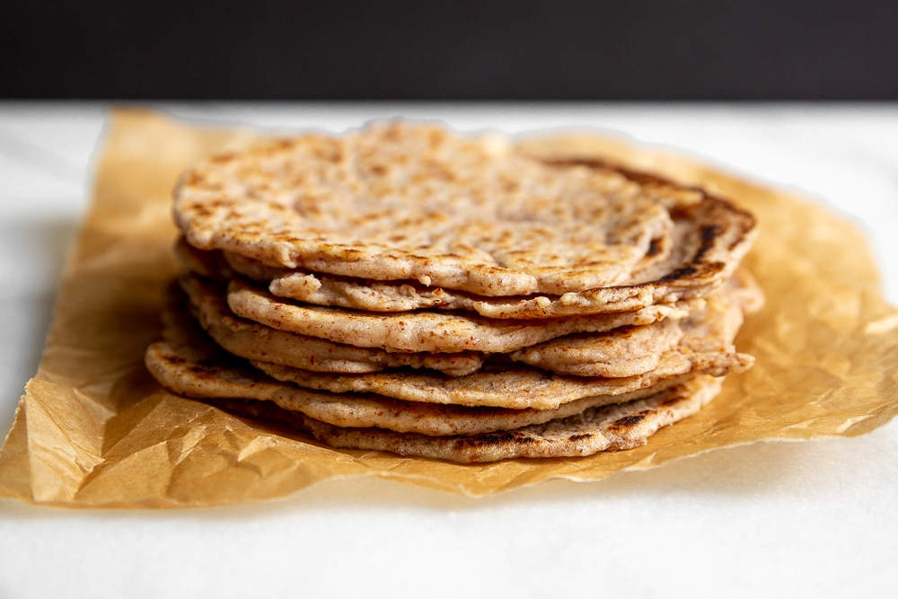 Cassava Tortillas stacked on a piece of parchment paper