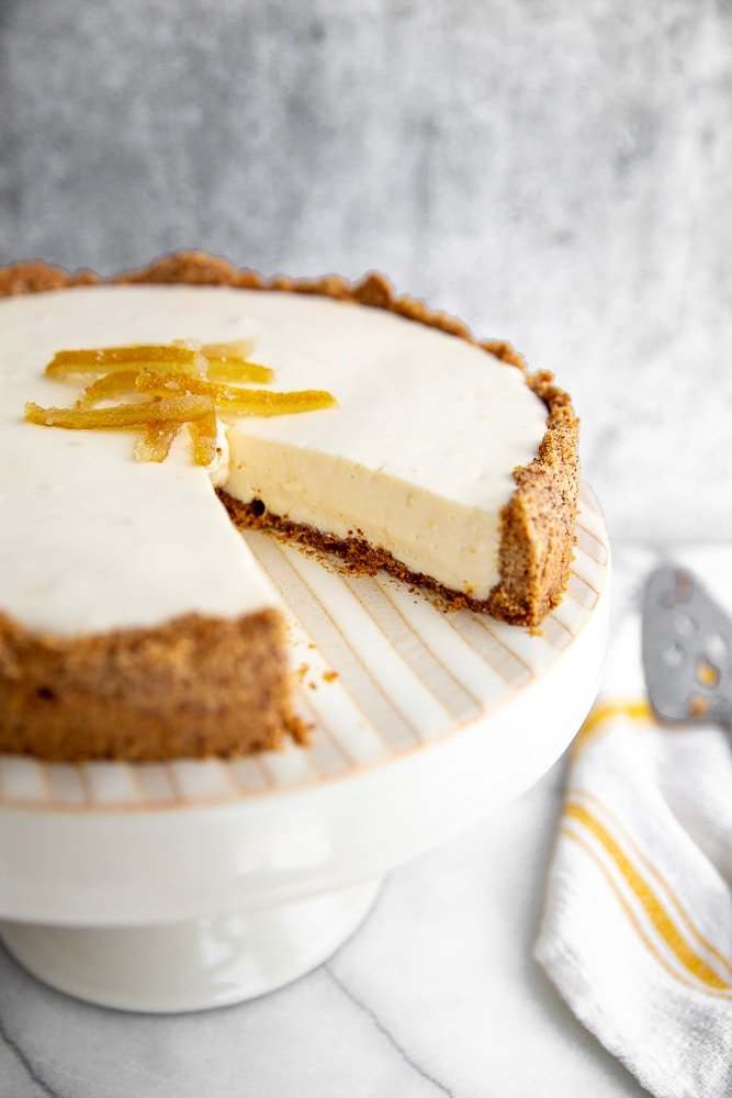 Creamy lemon pie with almond crust on cake stand with slice taken out
