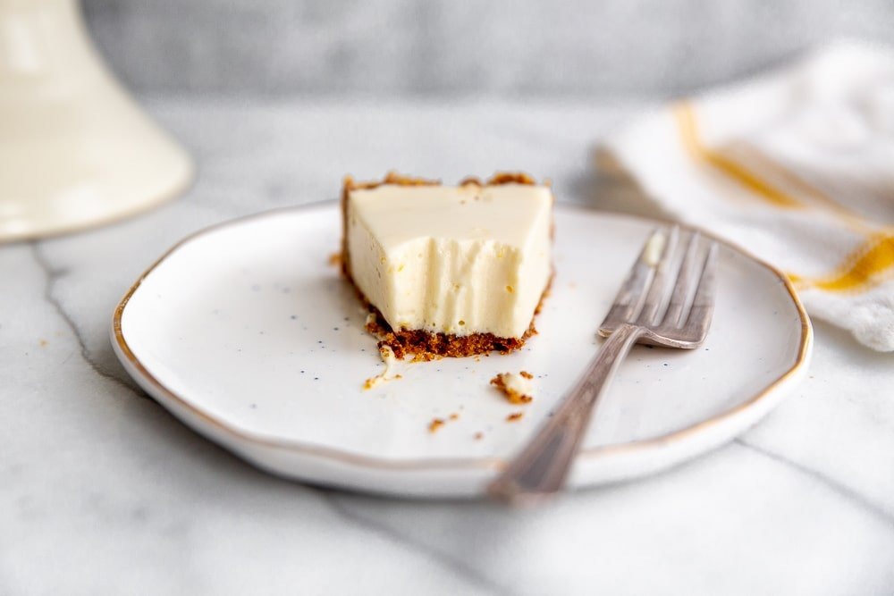 Slice of creamy lemon pie with almond crust on a plate with a fork