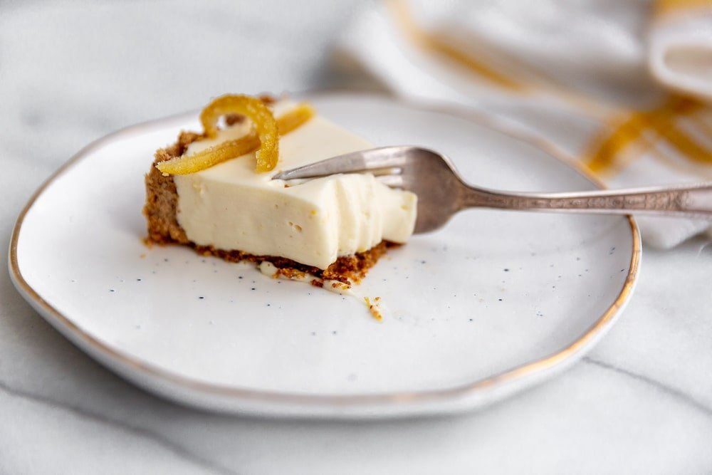 A slice of creamy lemon pie with almond crust on a plate with a fork going through it.