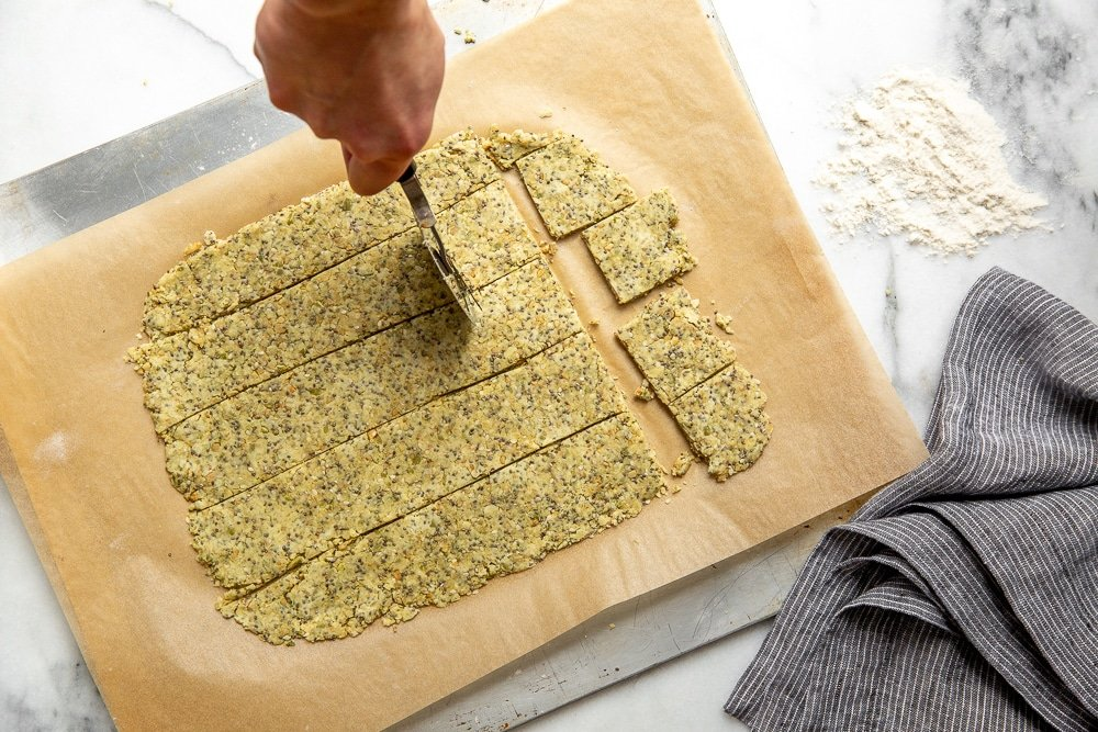 Seed cracker dough rolled out on a piece of parchment paper, with a hand cutting it into squares using a pizza cutter