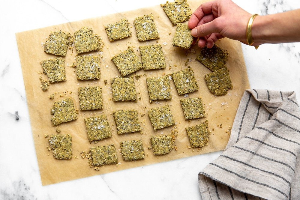 Seed crackers on parchment paper with a hand grabbing a cracker