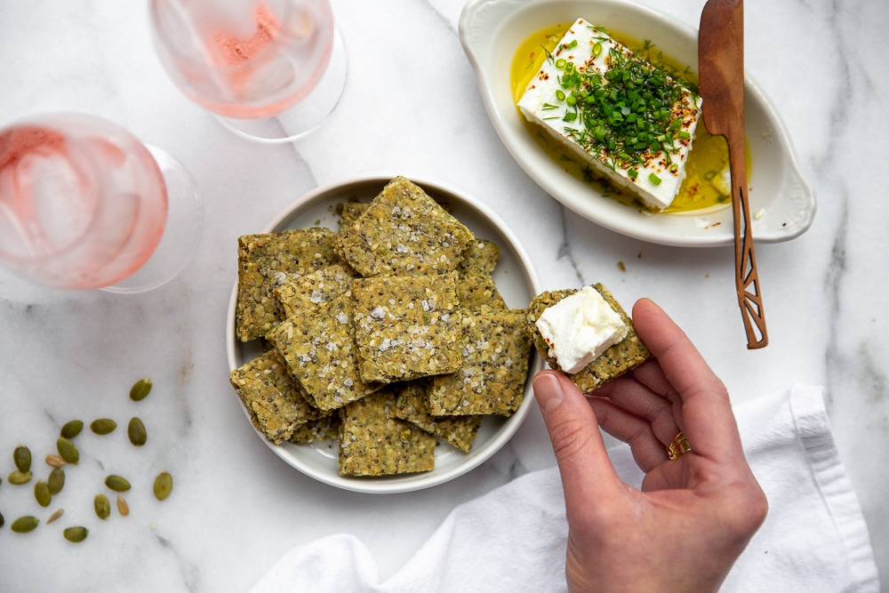 Hand holding a seed cracker topped with marinated feta