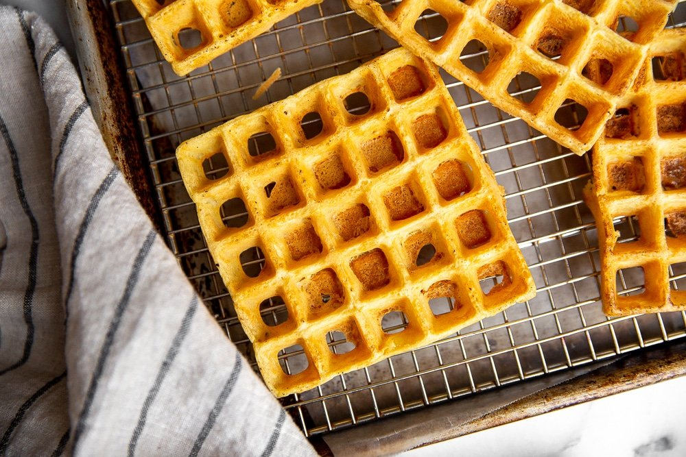 Chickpea waffles lined up on cooling rack set over sheet pan
