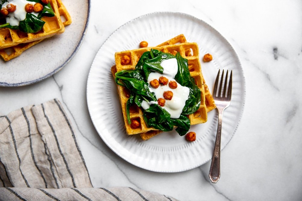 Two chickpea waffles stacked on plate, topped with sauteed spinach, yogurt and crispy chickpeas