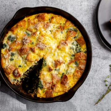 Vegetarian breakfast strata in a pan on the counter, with a piece taken out and on a plate