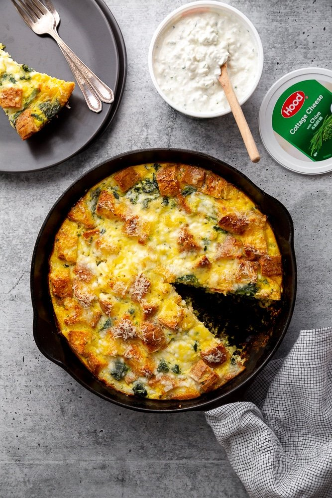 Vegetarian breakfast strata in a pan on the counter, with a wedge removed an on a plate