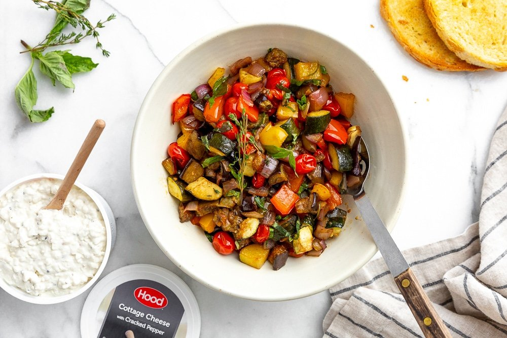 Ratatouille in serving bowl with toasted bread and cottage cheese alongside for serving