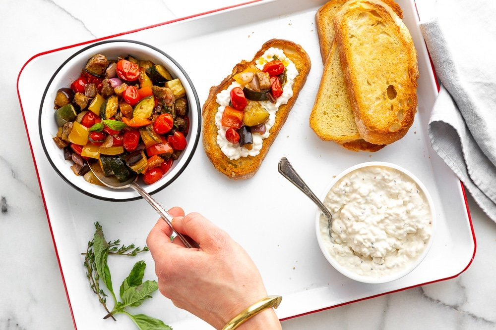 A tray holding a bowl of ratatouille, cottage cheese and toasted slices of bread, with a hand topping one of the pieces of bread