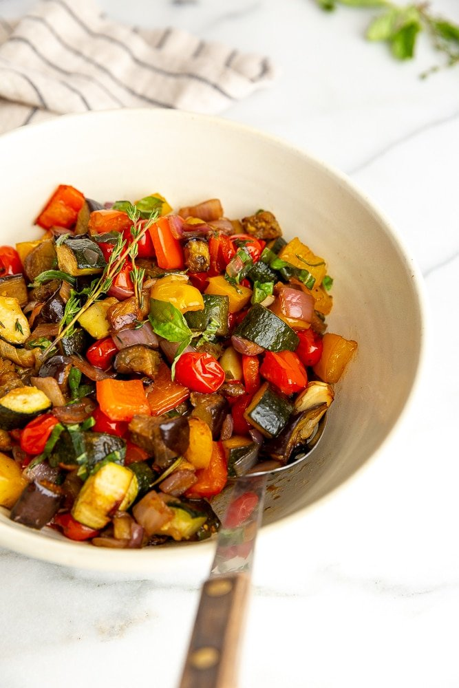 Ratatouille in large serving bowl with serving spoon