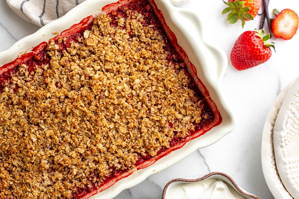 Gluten free strawberry crisp in baking dish with serving bowls alongside
