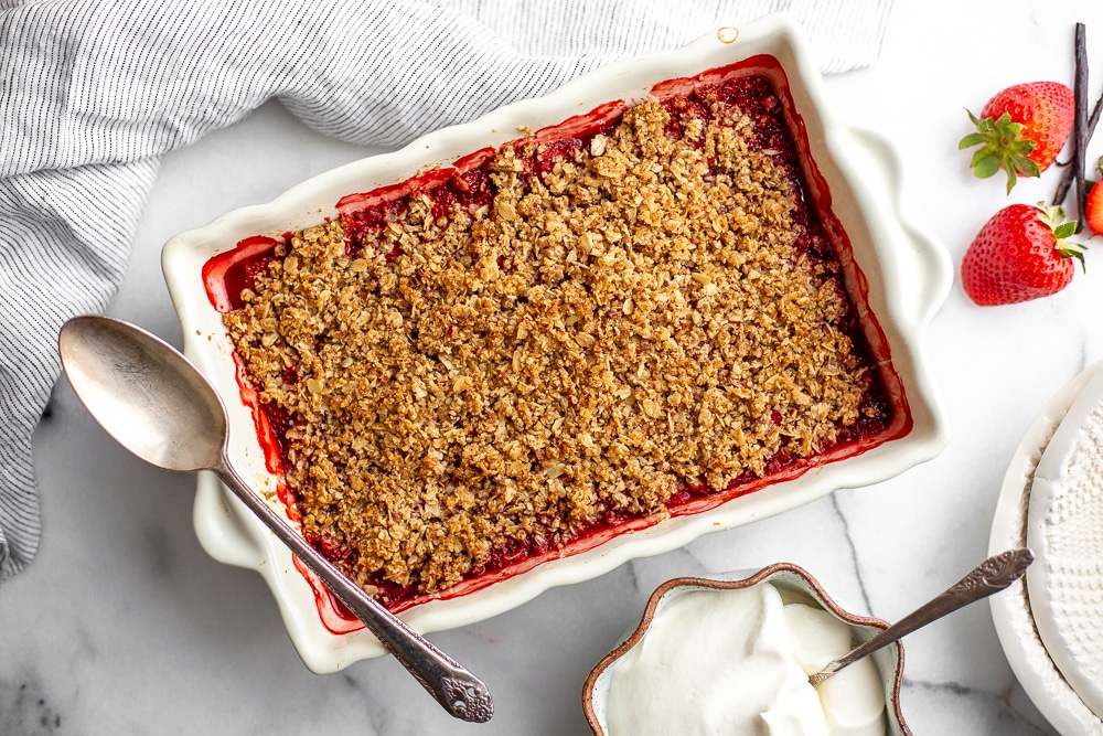 Gluten free strawberry crisp in baking dish with serving spoon and a bowl of whipped cream alongside