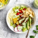 Healthy taco salad in bowl with jar of creamy cilantro lime dressing on the side