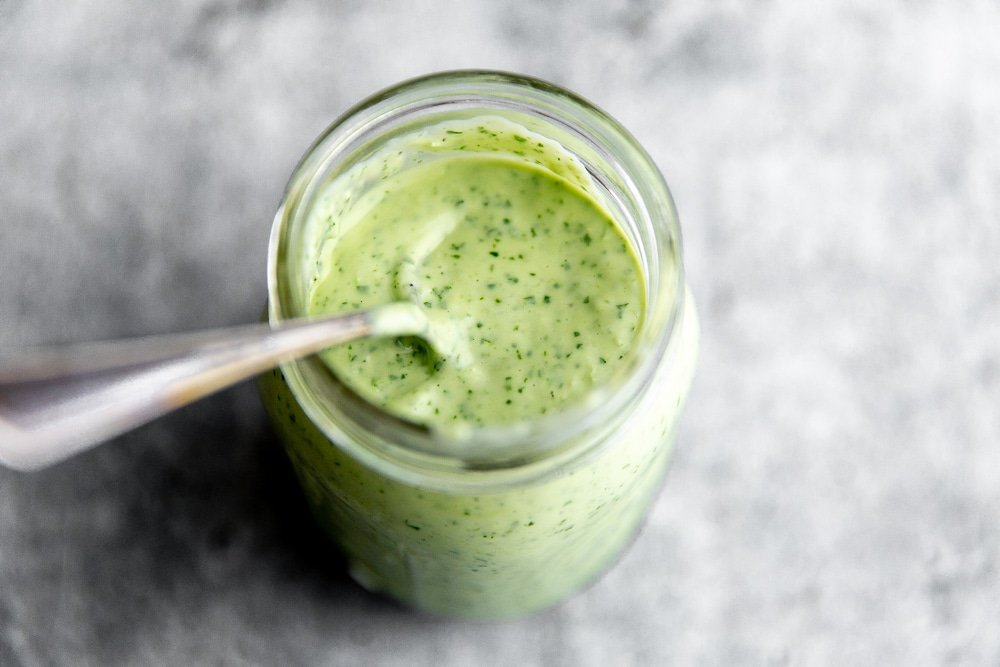 Creamy cilantro lime dressing in jar with spoon