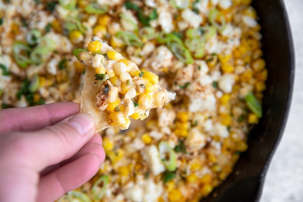 Hand holding tortilla chip topped with Mexican street corn dip.