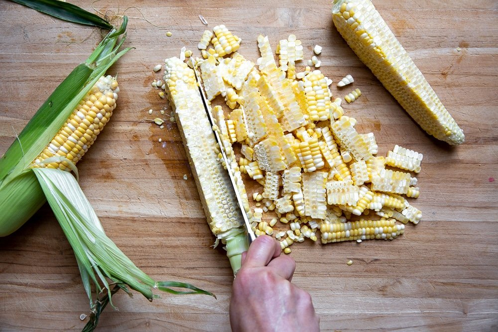 Process shot showing how to cut corn kernels off the cob.