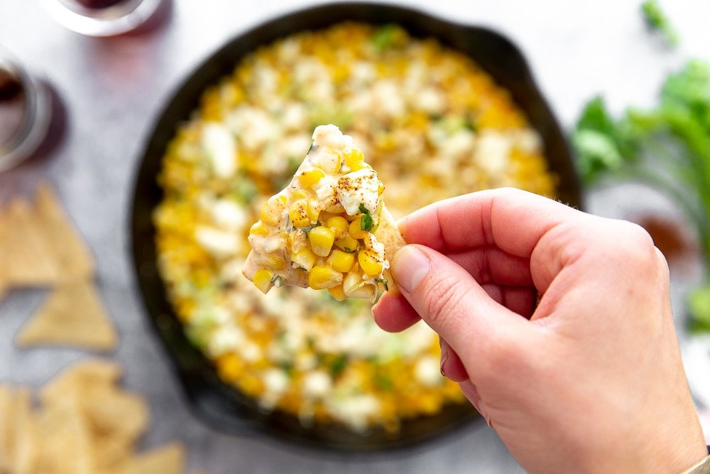 Close up overhead shot of hand holding tortilla chip topped with Mexican street corn dip.