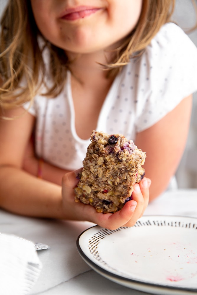 Child holding baked oatmeal bar in her hand.