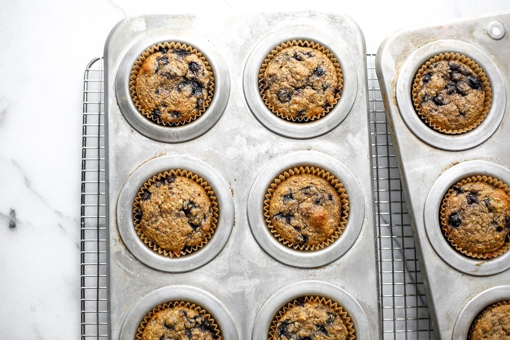 Blueberry blender muffins in muffin tin on cooling rack.