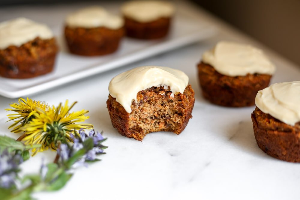 Close-up side-view of a carrot cake muffin on the counter with bite taken out.