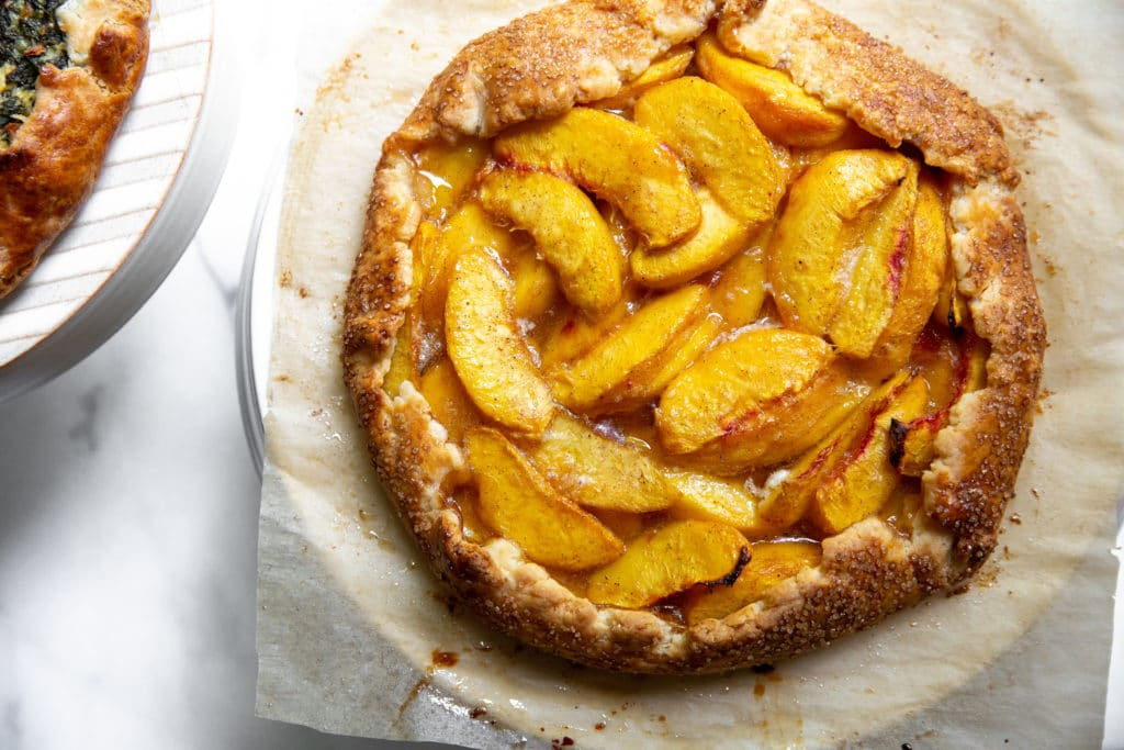 Overhead shot of a peach galette on a cake stand.