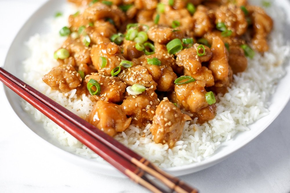 Close up of sesame chicken on a plate with rice.