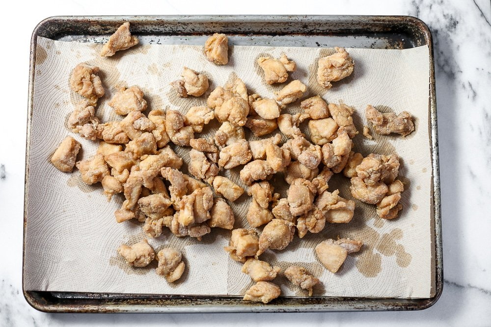 Fried chicken pieces draining on paper towels.
