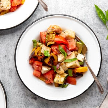 Grilled panzanella salad in serving bowls on table.