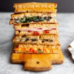 Oven grilled cheese sandwiches stacked on a serving board.