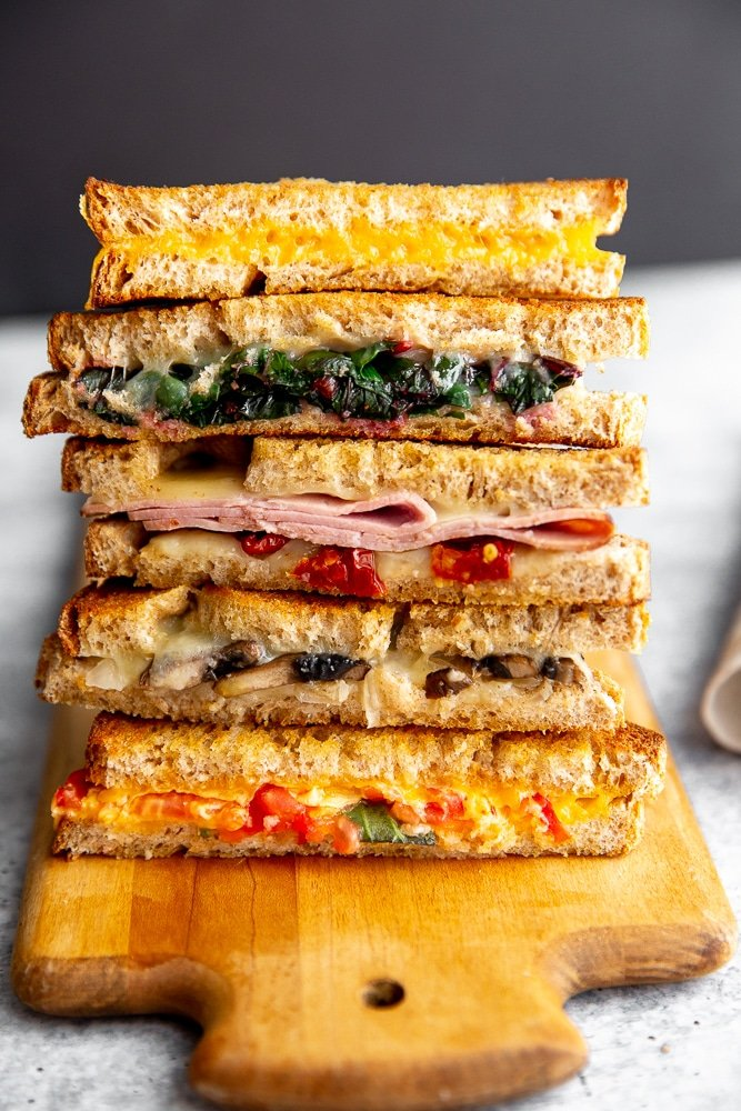 Grilled cheese sandwich halves stacked on a serving board.