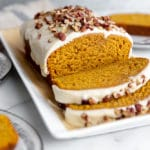 Sliced pumpkin pound cake on a platter with plates to the side.