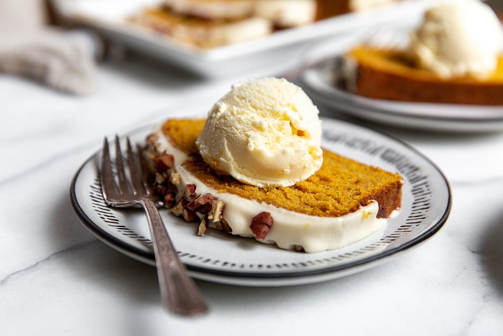 Pumpkin pound cake on plate with a scoop of vanilla ice cream on top.