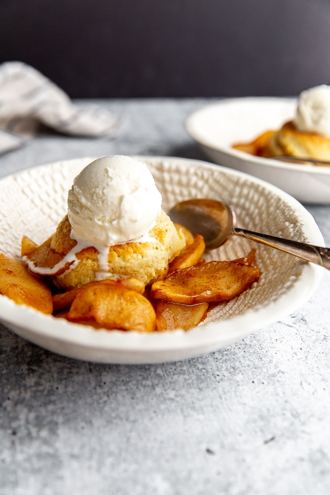 Close-up side view of the skillet apple cobbler in a bowl with a scoop of ice cream on top.