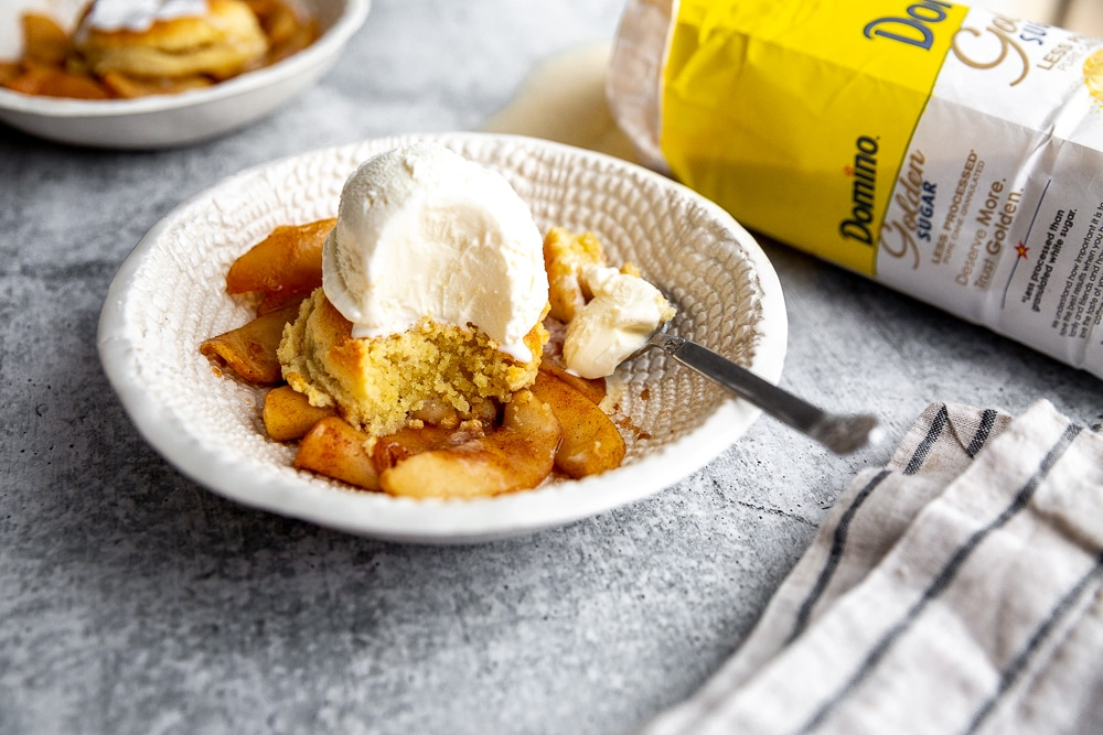 Apple skillet cobbler in a serving bowl with a scoop of ice cream on top.
