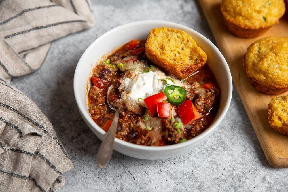 Bowl of chili with jalapeno cheddar cornbread muffins alongside.