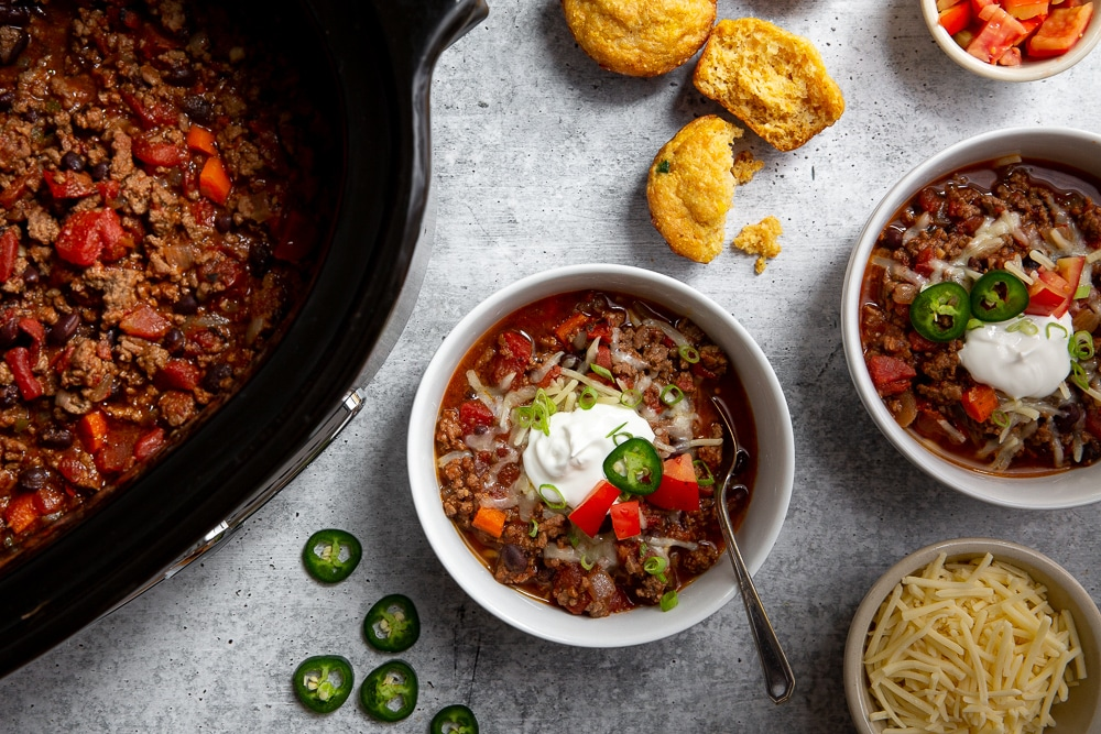 Overhead shot of two bowls of beef chili, with a slow cooker and toppings alongside.