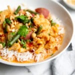 Close-up side view of vegetable massaman curry over rice in a serving bowl.