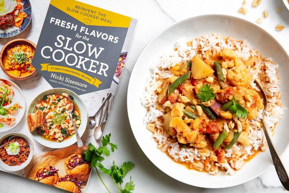 Overhead shot of bowl of curry with the book, Fresh Flavors for the Slow Cooker, alongside.