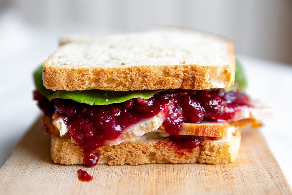 Close up of a turkey sandwich with cranberry sauce.