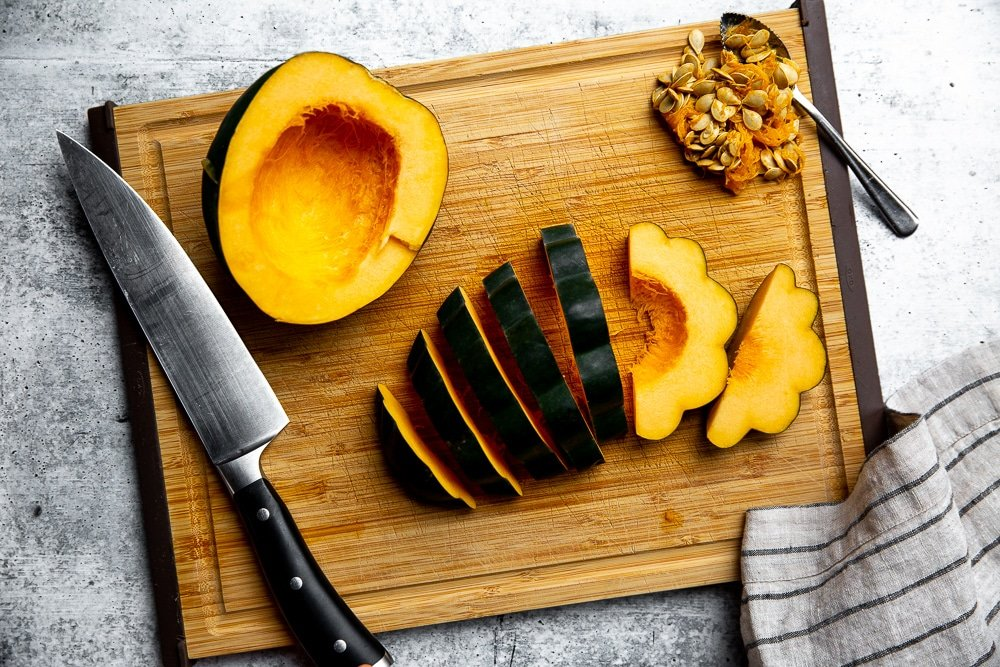 Process shot showing how to slice an acorn squash into half moons.